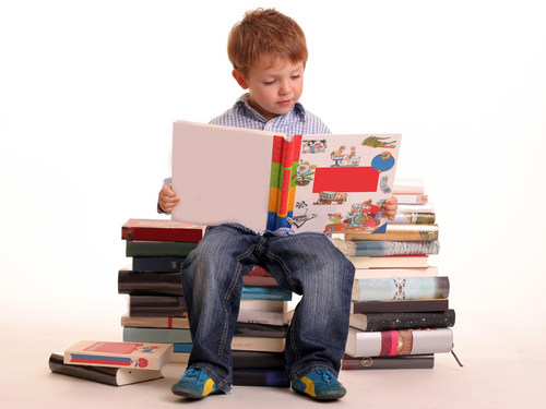 Child reading book sat on pile of books