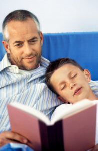 Close-up of father reading story to son (10-11)
