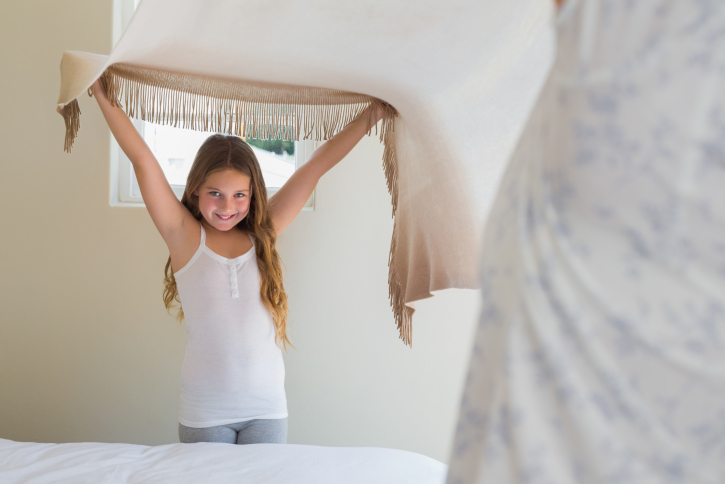 Happy little girl making bed