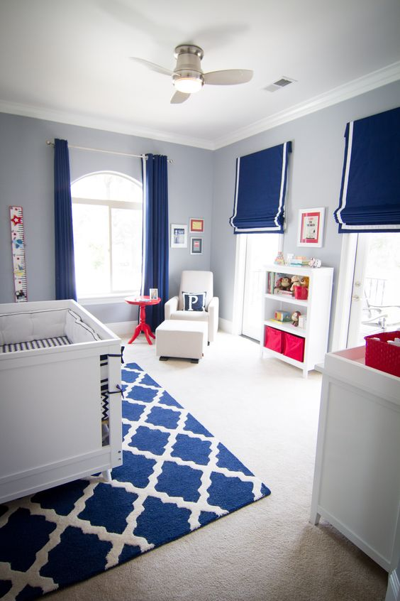 A well lit room with a cot on a blue and white rug