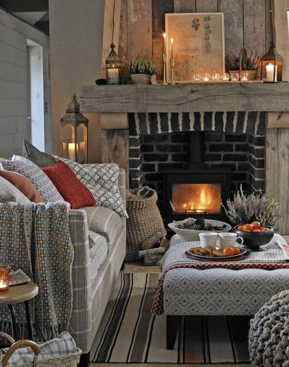 A room lit with candles above a fireplace, along with a cosy couch