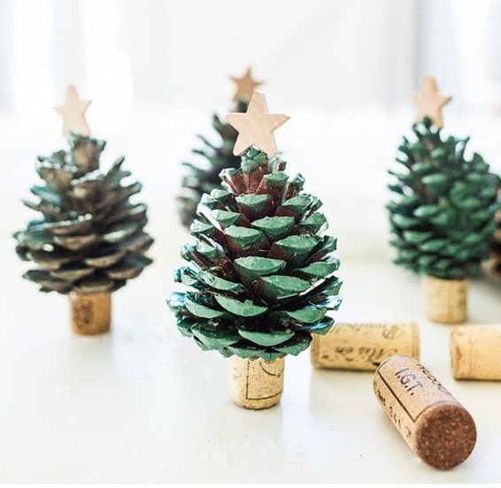 Painted pine cones with a wooden star, to look like small Christmas trees