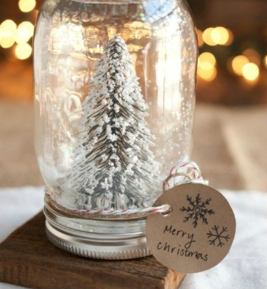 A small fake tree with fake snow in a jar