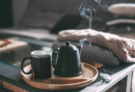 Green teapot and mug on a wooden tray on top of a coffee table