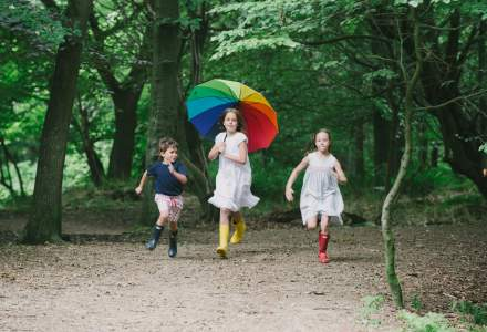 Three children running with a multi coloured umbrella