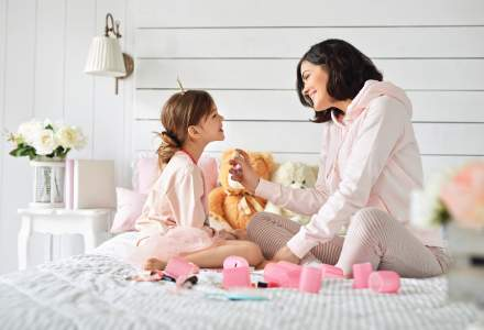 Mother and daughter sit on white bed while smelling fragrances.