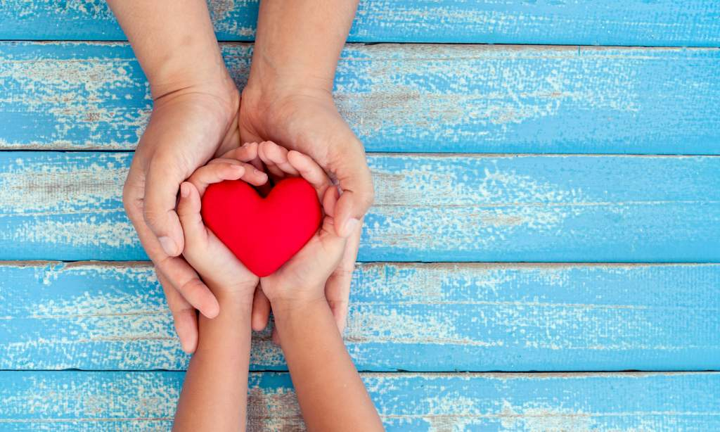 Parent and child hold a red love heart on a blue picnic bench.
