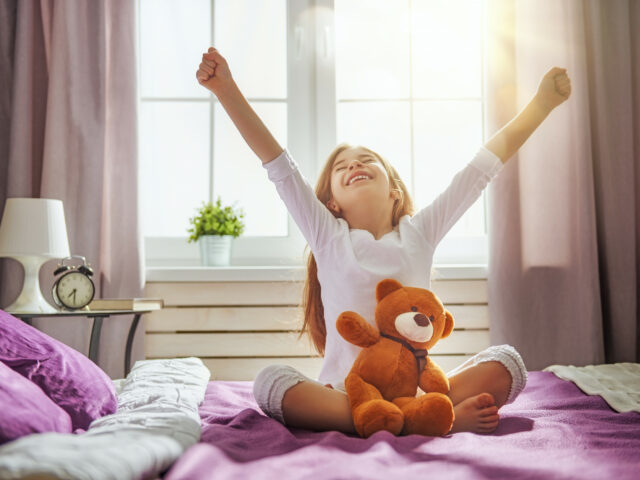 The sun is shining through the window as a girl stretches on a bed.