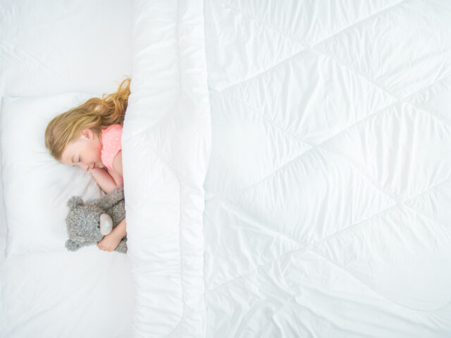 Young girl sleeps in a white bed while cuddling a grey teddy.