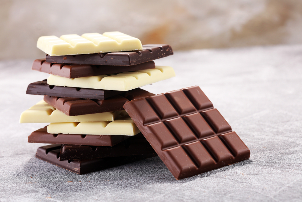 Milk, white and dark chocolate stacked high on a table.