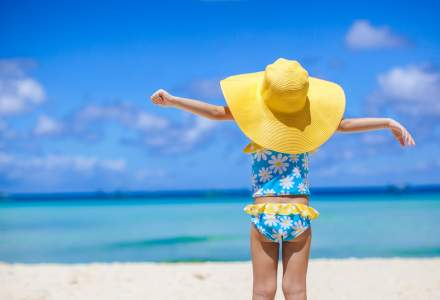 Child wearing blue swimming costume with white flowers stands on a sunny beach with her arms stretched out in the air.