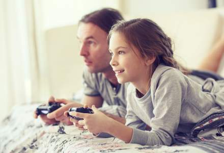 A young girl and her dad lay on a bed playing video games.