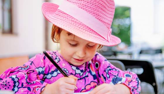 Young girl wears a pink hat and top while writing in a diary.