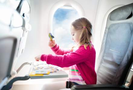 A young girl sits on an aeroplane wearing a pink cardigan.
