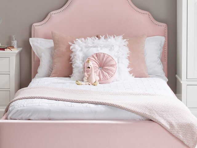 Pink upholstered bed from Room to Grow.