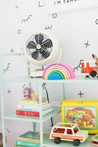 A white fan sits on a pastel green shelf in a child's bedroom.
