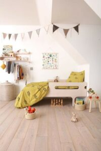 A child's bedroom with wooden flooring, a wooden starter bed and neutral bunting.