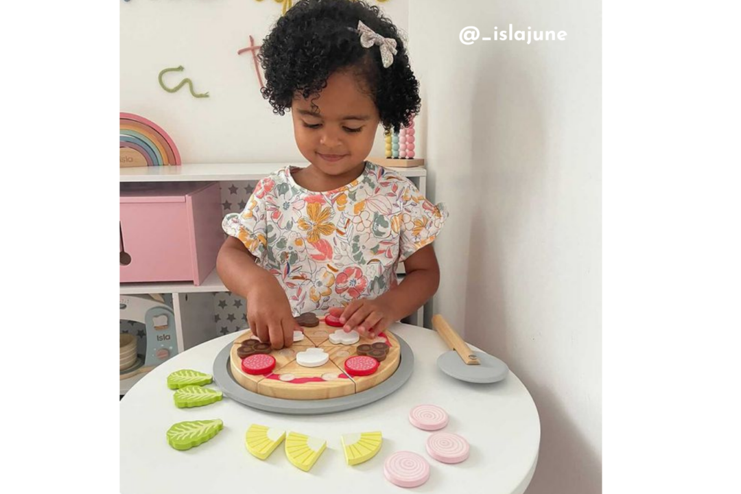 Little girl plays with pretend wooden toy pizza set.