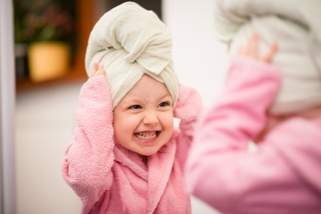Child with towel and bath robe at bath time