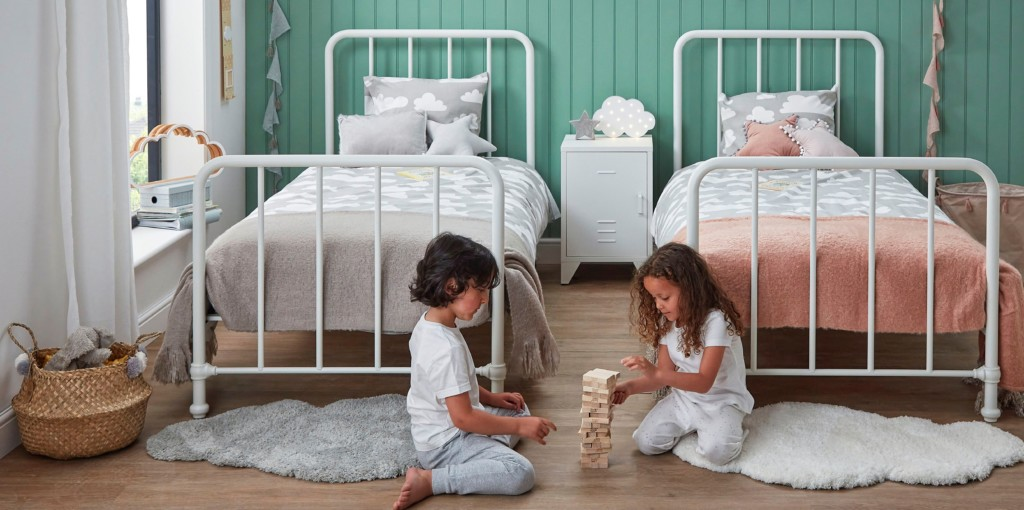 A 5 year old boy and a 5 year old girl play blocks together on the bedroom floor between two single beds.