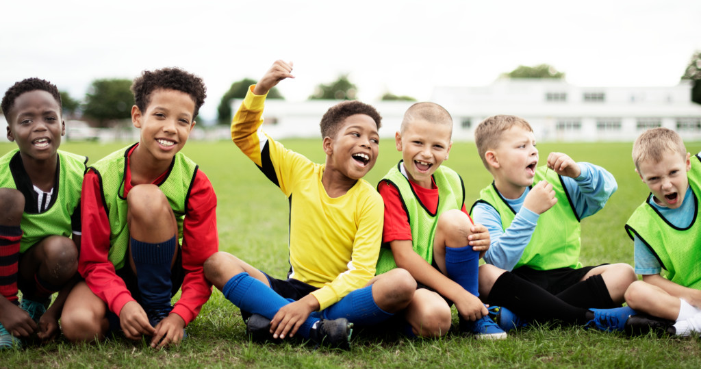 A group of boys in football wear enjoy celebrating their win together by smiling and laughing.