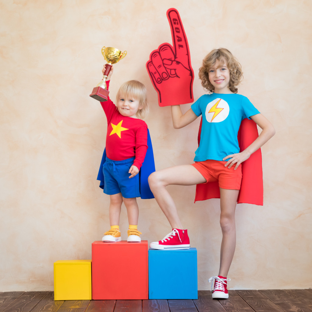 Two brothers on an olympic style podium. One holds a trophy and the other is holding a foam finger. They are dressed as super heroes with red and blue capes.
