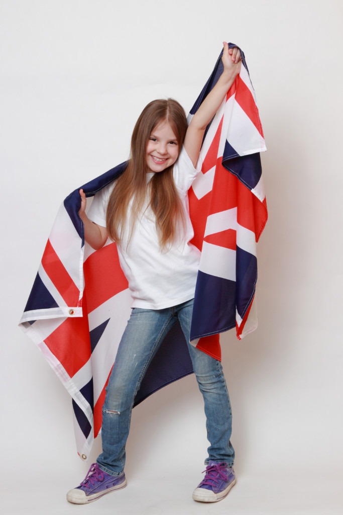 A young girl proudly holds a union jack flag to represent team GB.