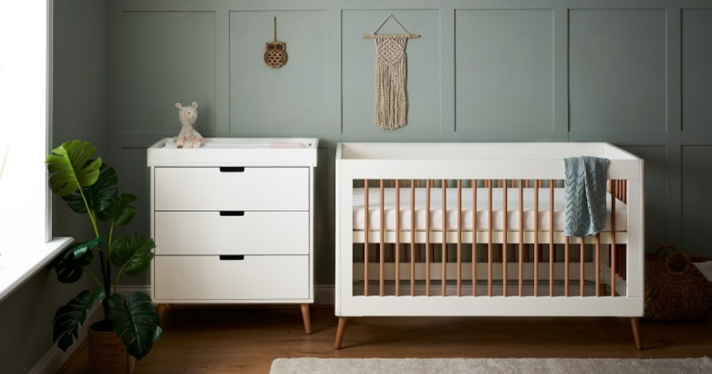 A nursery room is painted green and has a white changing table and dresser on the left against the back wall. On the right against the back wall is a white and natural wood coloured cot bed.