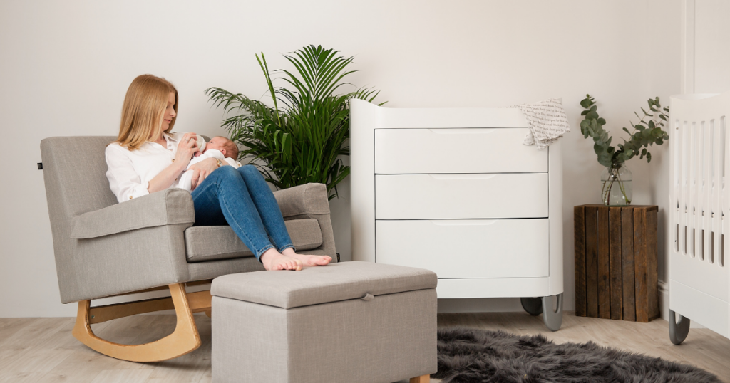 A parent bottle feeds their baby whilst sitting on a rocking nursing chair and resting their feet on a storage footstool. The chair and the footstool are grey. In the room is also a changing dresser in white and a cot bed in white. There is a large grey fluffy rug on the floor.