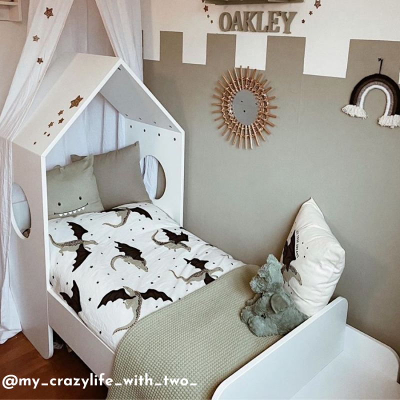 A white toddler sized bed with a feature roof is in a bedroom decorated in a dragons and castles theme, that has a green colour scheme.