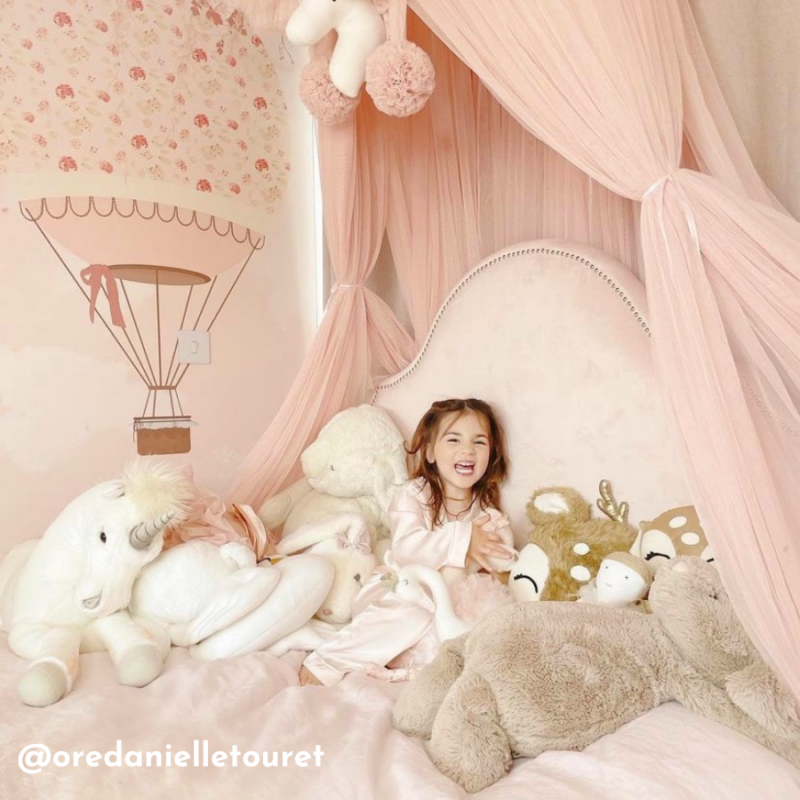 A little girl sits in a pink upholstered velvet bed surrounded by teddies. She is smiling and the theme is pink princesses and there is a wallpaper feature of a pink hot air balloon on the wall.