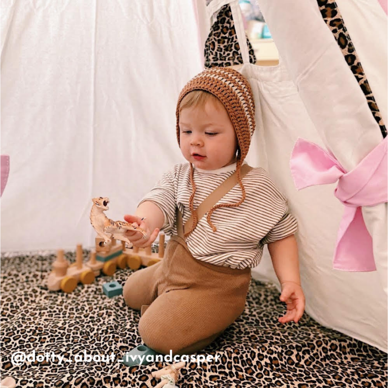 A toddler boy sits inside a teepee and plays. The teepee is pink, white and leopard animal print in colour.