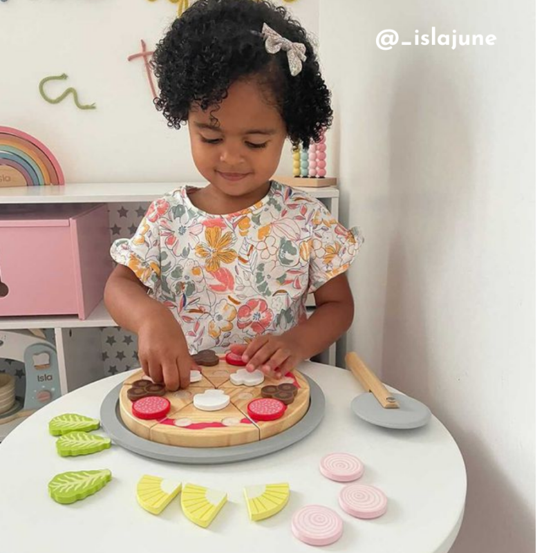 A little girl plays with a pretend pizza toy set on a small childrens table. She is standing and putting toppings on the pretend pizza.