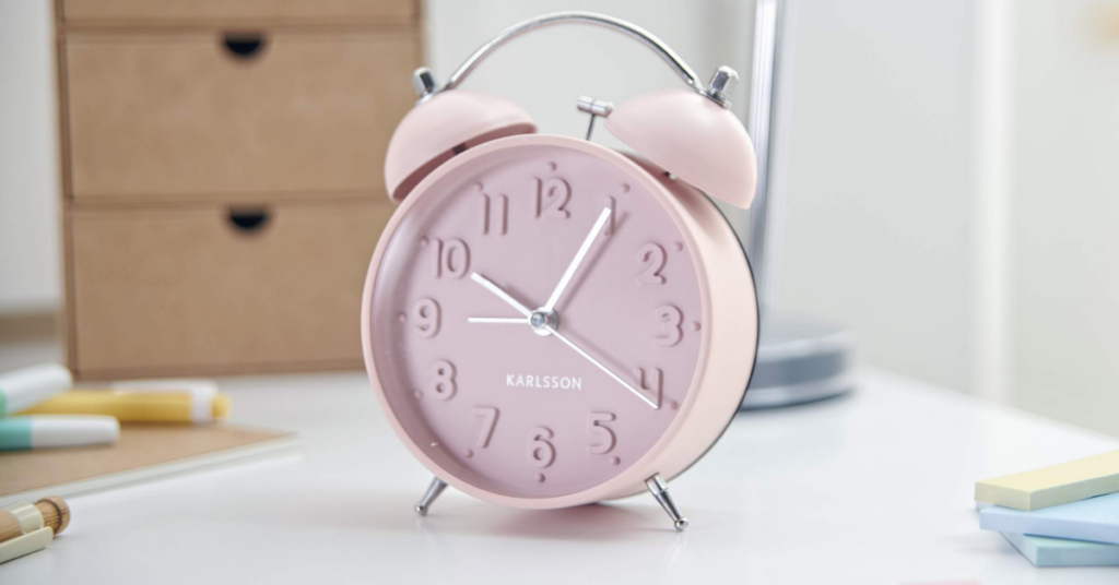 A pink metal old style alarm clock for children sits on a children's bedside table.